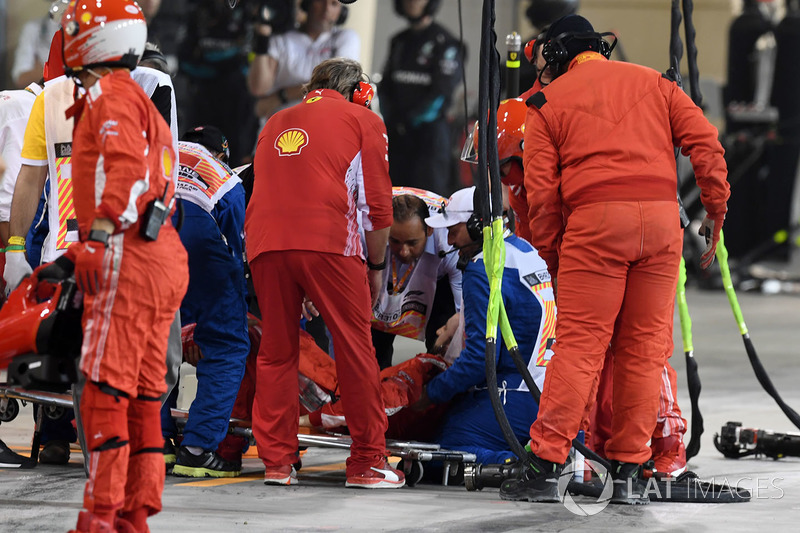 A Ferrari mechanic is tended by medics after being hit by the car of Kimi Raikkonen, Ferrari SF71H d