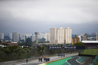 The Sao Paulo skyline behind the circuit In the foreground, Pierre Gasly, Toro Rosso, and team members walk the circuit, along with Sergio Perez, Force India