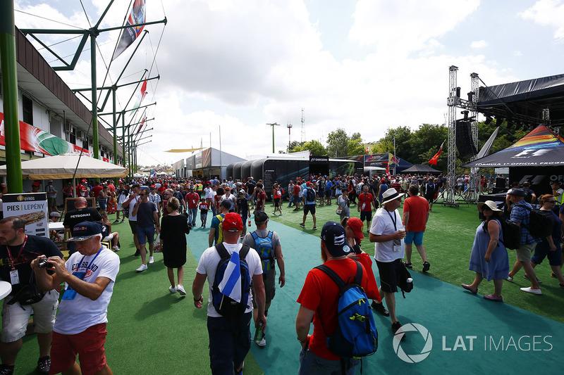 Fans walk past merchandise stalls behind a grandstand