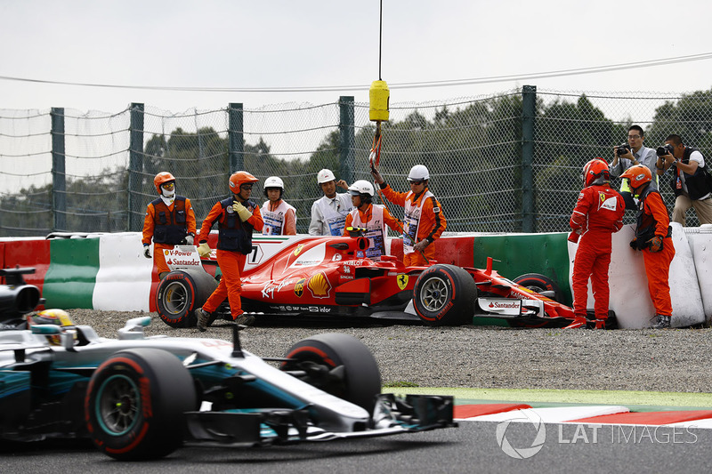 Lewis Hamilton, Mercedes AMG F1 W08, passes the crashed car of Kimi Raikkonen, Ferrari SF70H, as marshals recover it