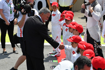 Chase Carey, Chief Executive Officer and Executive Chairman of the Formula One Group and grid kids on the grid