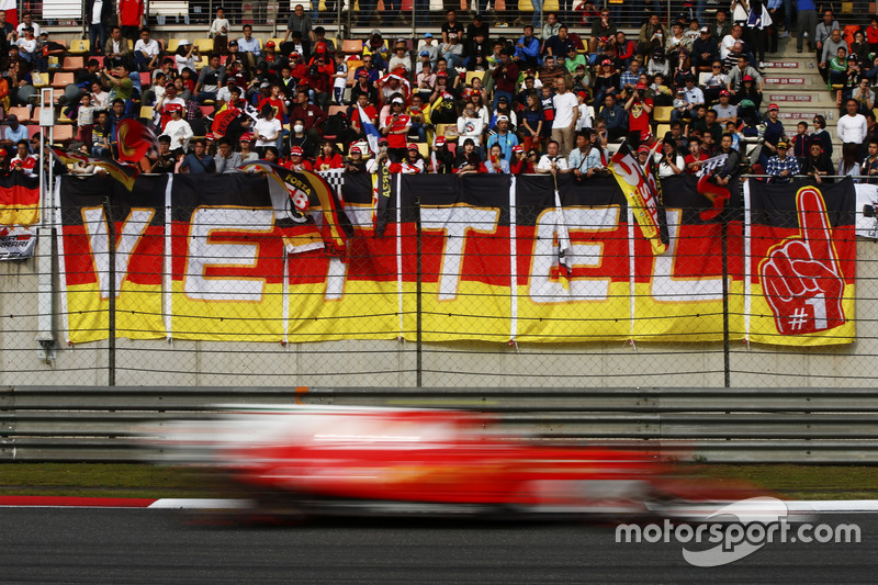A Ferrari flashes by a stand containing a large number of Sebastian Vettel, Ferrari, fans