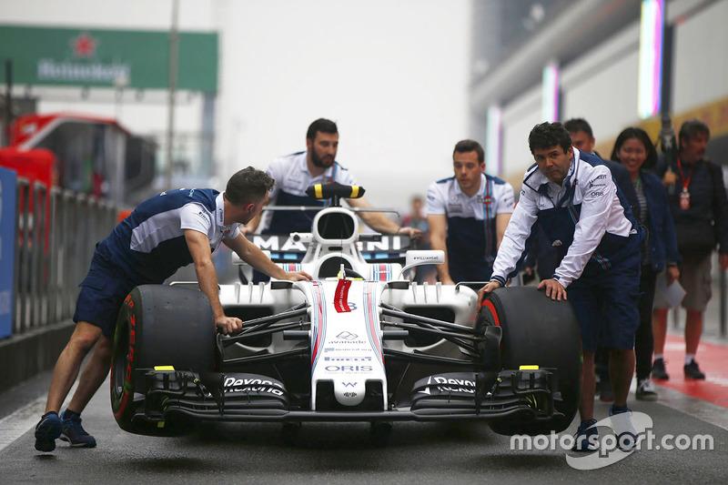 Los miembros del equipo Williams empujan un FW40 Williams