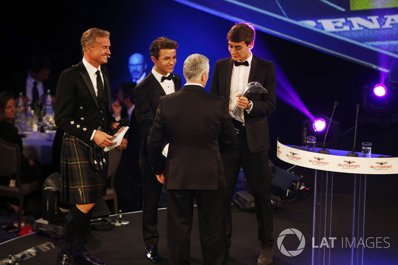 Derek Warwick is presented with an award by Lando Norris and George Russell