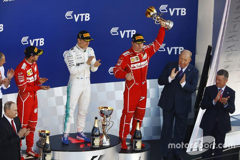 Third place Kimi Raikkonen, Ferrari, lifts his trophy alongside Race winner Second place Valtteri Bottas, Mercedes AMG F1 Sebastian Vettel, Ferrari