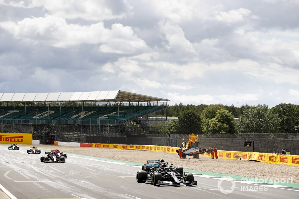 Lewis Hamilton, Mercedes F1 W11, Valtteri Bottas, Mercedes F1 W11, and Max Verstappen, Red Bull Racing RB16, as they pass the crashed car of Kevin Magnussen, Haas VF-20