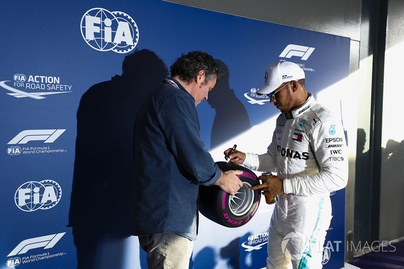 Lewis Hamilton, Mercedes AMG F1, signs a miniature Pirelli tyre after taking pole position