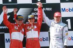 Podium: winner Michael Schumacher, Ferrari, second place Eddie Irvine, Ferrari, third place Mika Hakkinen, McLaren