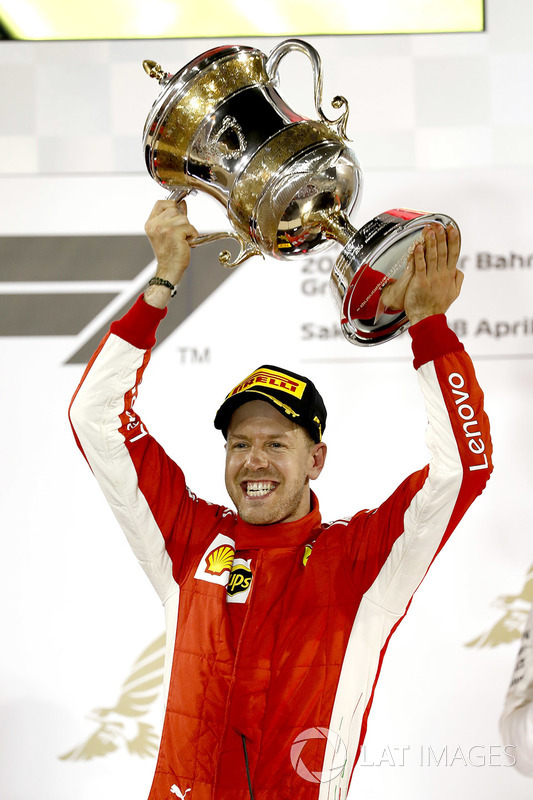 Sebastian Vettel, Ferrari, 1st position, lifts his trophy on the podium