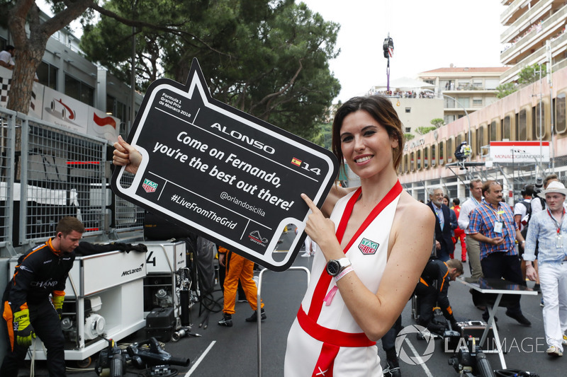 A grid girl holds a promotional board for Fernando Alonso, McLaren