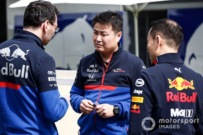 Red Bull Racing Honda and Toro Rosso Honda personnel talk in the pit lane
