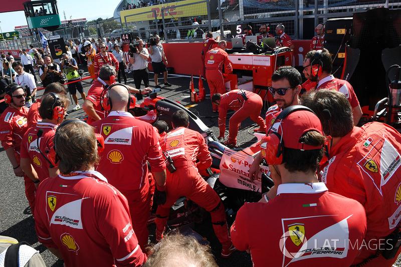 I meccanici Ferrari osservano la monoposto di Sebastian Vettel, Ferrari SF70H, con problemi tecnici