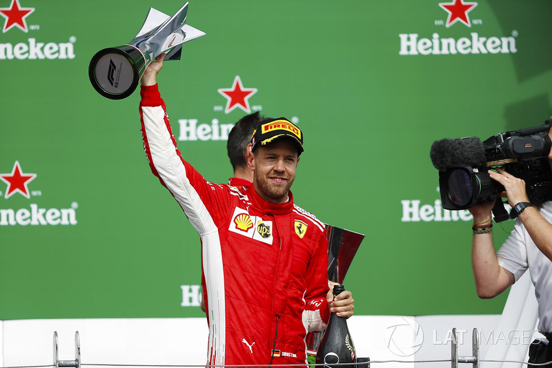 Sebastian Vettel, Ferrari, is filmed raising his winner's trophy on the podium