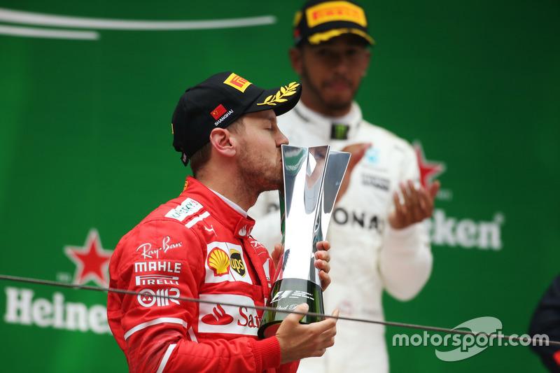 Sebastian Vettel, Ferrari kisses his trophy on the podium
