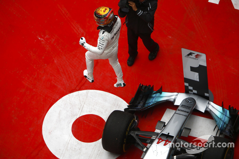 Lewis Hamilton, Mercedes AMG, leaps off his car in parc ferme after taking victory