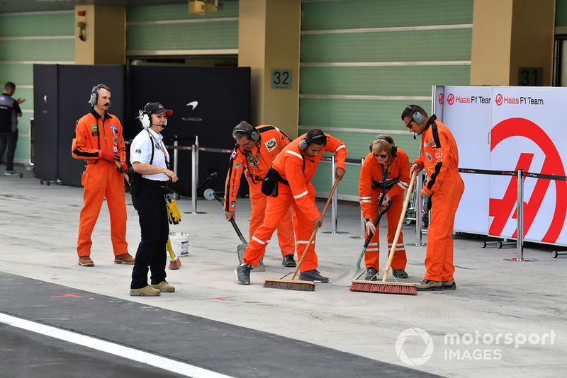 Marshals clean the Haas F1 pit box