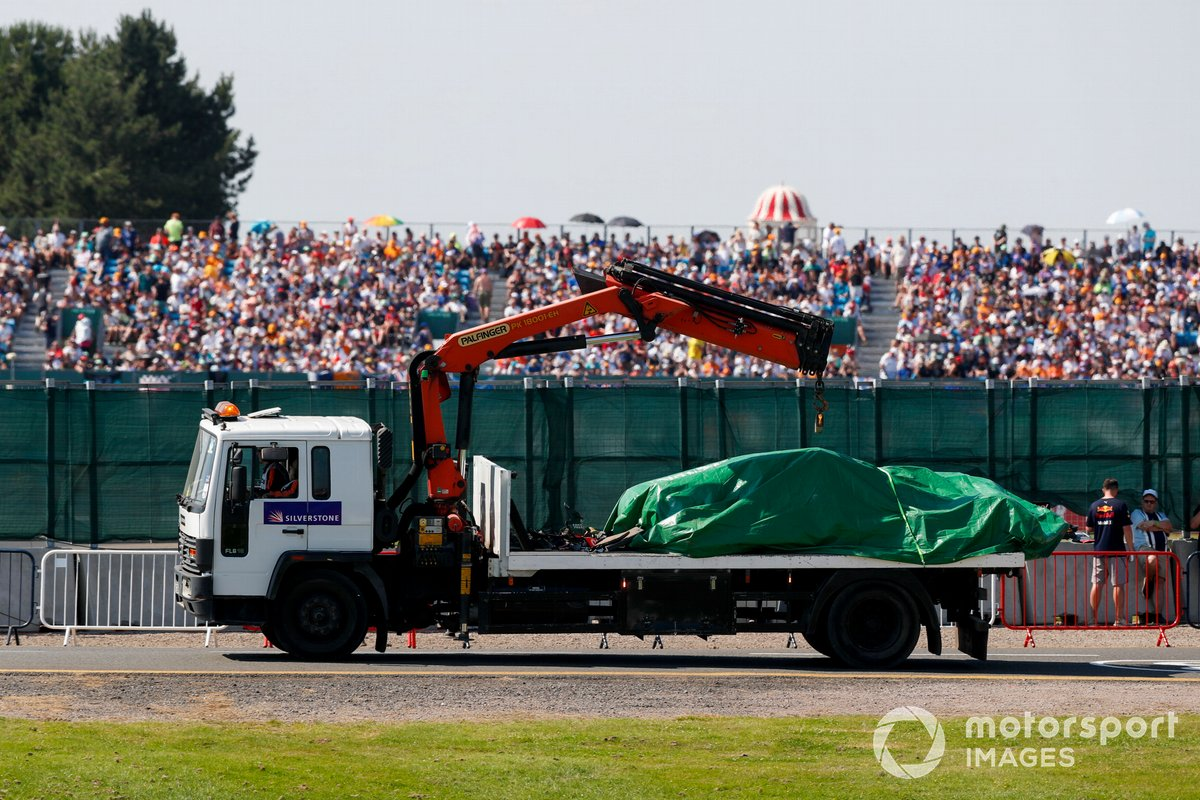 The car of Max Verstappen, Red Bull Racing RB16B, is returned to the garage on a truck under a tarpaulin