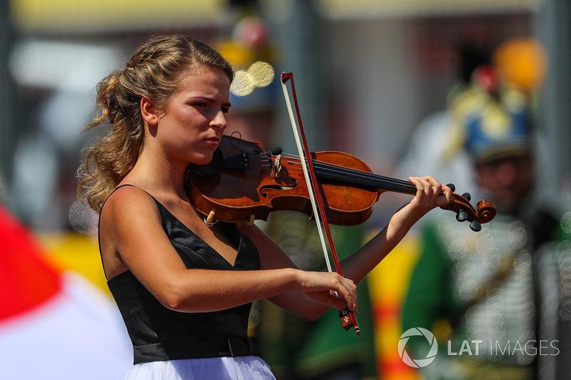 Una chica toca el himno nacional
