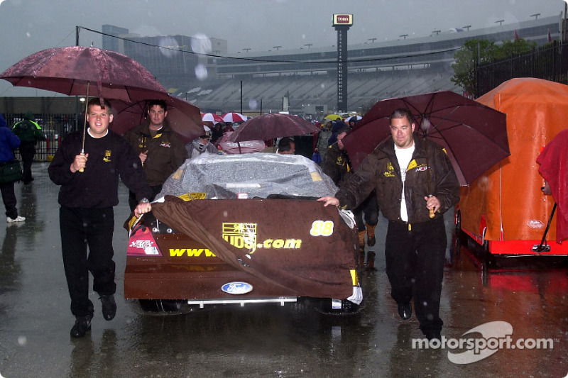 Dale Jarrett's UPS Ford is pushed back to the garage area through the downpour