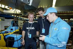 Fernando Alonso mostrándole al nadador Pieter van den Hoogenband y al patinador holandés de velocidad, Jochem Uytdehaage, el volante del Renault F1