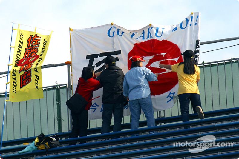 Los aficionados de Takuma Sato instalan sus letreros