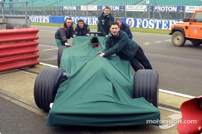 Jaguar Racing crew members push the Jaguar back to the garage area