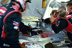 Crew works on Kurt Busch's damaged car