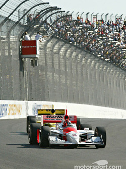 Helio Castroneves takes the checkered flag ahead of Sam Hornish Jr.