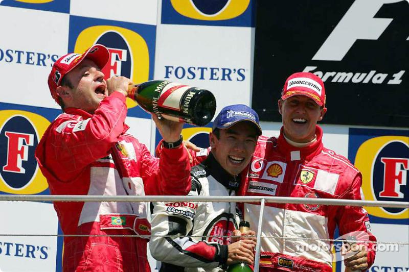 Сато на подиуме Гран При США 2004 года вместе с Рубенсом Баррикелло и Михаэлем Шумахером