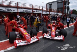 Rubens Barrichello and Michael Schumacher pushed back in the garage