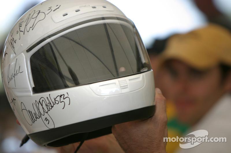 Drivers sign autographs on an helmet
