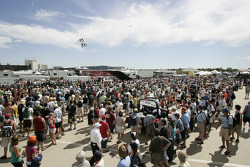 The large Friday crowd watches motorcycle jumpers as they wait for the Champ Car autograph session to begin