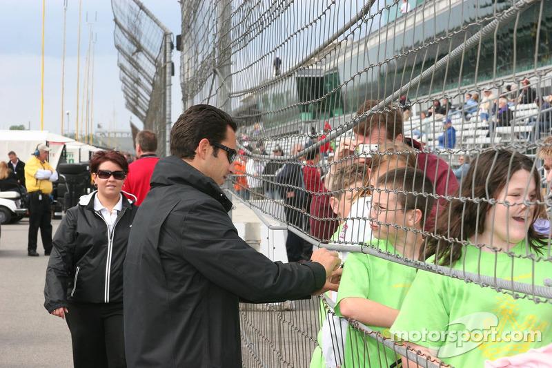 Helio Castroneves signe des autographes pour des écoliers