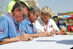 Johnny Rutherford and Al Unser Sr. sign a banner