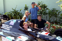 Tennis stars Anna Kournikova and Jan-Michael Gambill are shown an IRL IndyCar Series racecar by Helio Castroneves and Gil de Ferran following an exhibition tennis match at the Tennis Center at Crandon Park in Key Biscayne