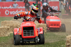 Craig Lowndes takes part in a lawn mower race