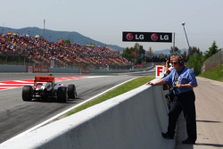 Jo Bauer, FIA Delegate, watches Narain Karthikeyan, HRT Formula One Team HRT leaves the pits