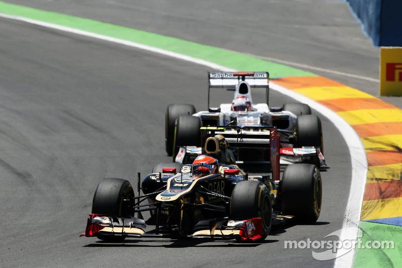 Romain Grosjean, Lotus F1 leads Kamui Kobayashi, Sauber