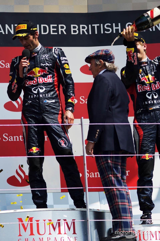 Sebastian Vettel, Red Bull Racing pours champagne on Jackie Stewart, on the podium as race winner Mark Webber, Red Bull Racing talks to the crowd