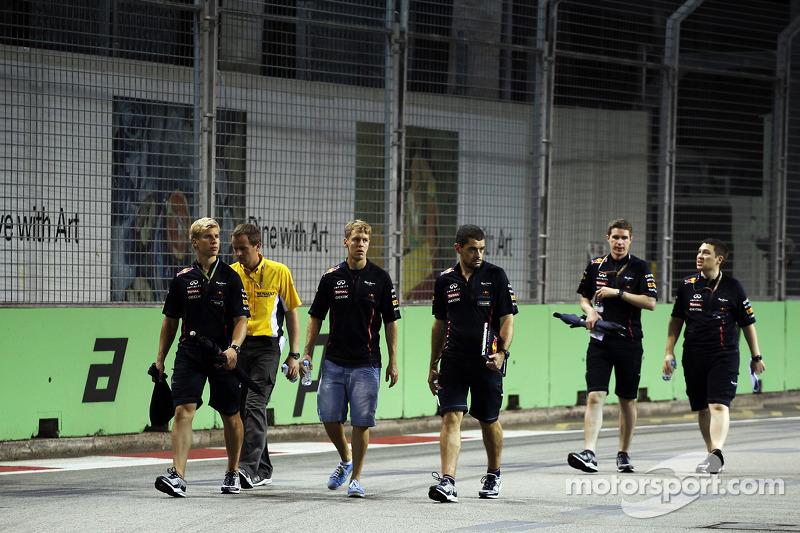 Sebastian Vettel, Red Bull Racing wandelt op het circuit met Heikki Huovinen, Personal Trainer, en Guillaume Rocquelin, Red Bull Racing Race Engineer,