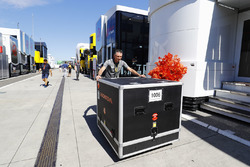 A container of McLaren Honda equipment is pushed through the paddock