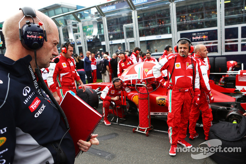 Adrian Newey, Red Bull Racing Chief Technical Officer kijkt naar de Ferrari F138 op de grid