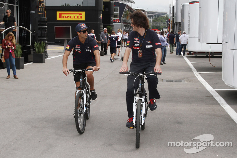 Daniel Ricciardo, Scuderia Toro Rosso rides his bike through the paddock