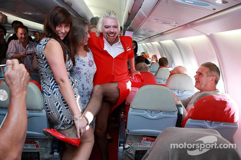 Sir Richard Branson serves as a flight attendant on Air Asia flight after losing a bet with Caterham F1 boss Tony Fernandes