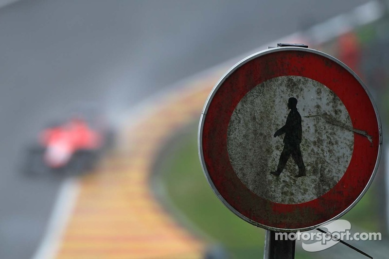 A Marussia F1 Team MR02 passes an old road sign