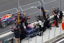 Race winner Sebastian Vettel, Red Bull Racing RB9 celebrates past his team at the end of the race