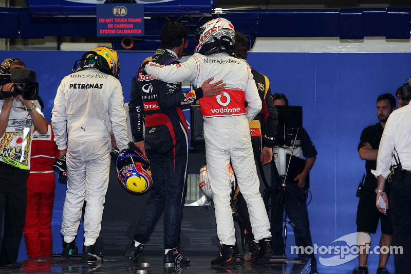 Jenson Button, McLaren, congratulates Mark Webber, Red Bull Racing, on his pole position in parc fer