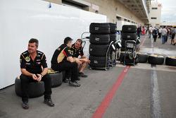 Lotus team members take a break in the paddock