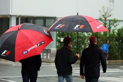 Anthony Davidson, apresentador da Sky Sports F1, e Johnny Herbert, apresentador da Sky Sports F1, debaixo de guarda-chuvas no paddock