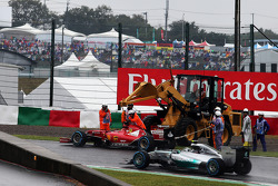 Nico Rosberg, Mercedes AMG F1 W05 passes the stricken Ferrari F14-T of Fernando Alonso, Ferrari, which is removed by marshals using a digger